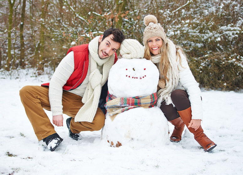 31000387 - happy couple posing with a snowman outside in winter